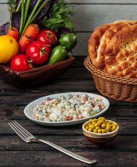 Salade olivier dans un petit plat blanc servi avec des pois verts