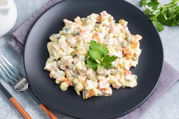 Salade d'olivier avec mayonnaise sur une assiette