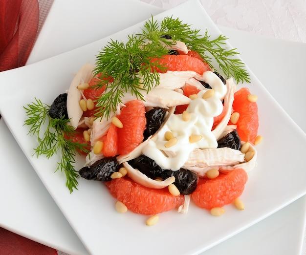 Salade de pamplemousse et pruneaux au poulet, recouverte de yaourt aux pignons de pin