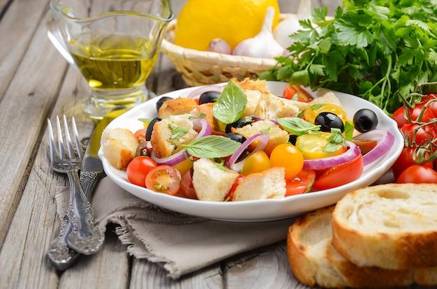 Salade panzanella italienne traditionnelle avec des tomates fraîches et du pain croustillant.