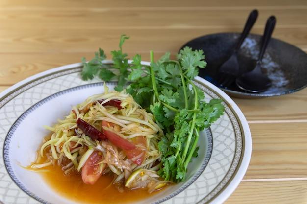 Salade de papaye et de coriandre dans un plat prêt à manger sur la table, la nourriture populaire asiatique.