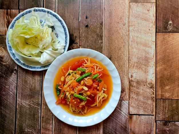 Salade de papaye cuisine thaïlandaise épicée sur fond de bois