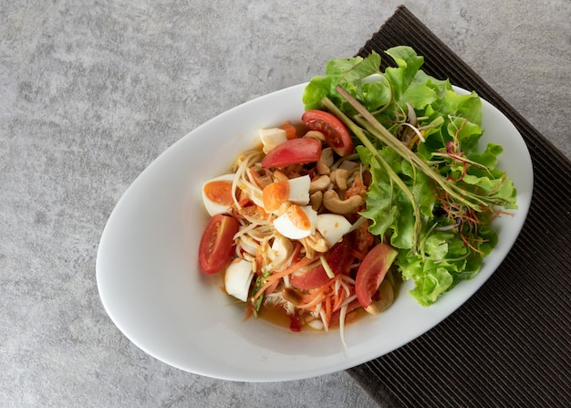 Salade de papaye avec des œufs salés sur une assiette, somtum ou salade de papaye thaïlandaise