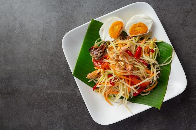 Salade de papaye servie avec nouilles de riz et salade de légumes décoré avec des ingrédients thaïlandais.