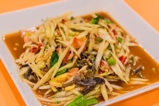 La salade de papaye ou le som-tam dans une assiette est placé sur la table orange.