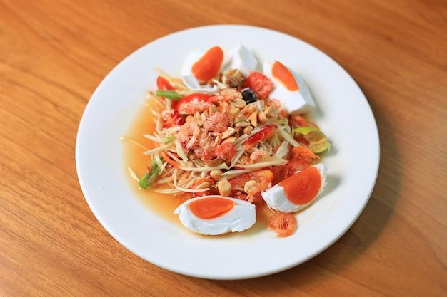 Salade de papaye (som tam) avec œuf salé et crevettes les aliments traditionnels thaïlandais sur fond de table en bois. nourriture populaire la plus recherchée en thaïlande