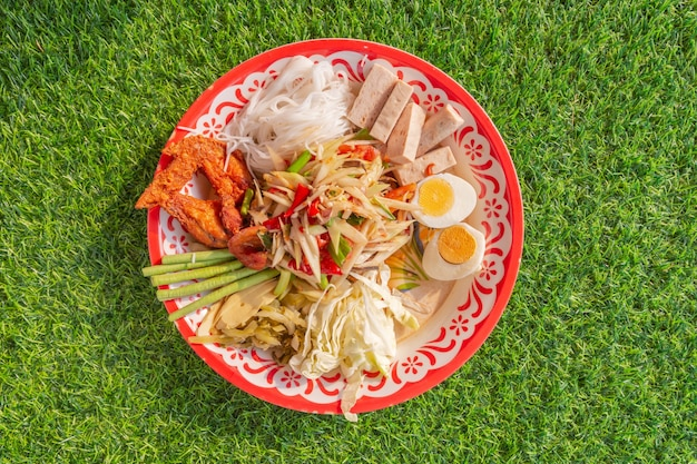 Salade de papaye (som tum) plateau épicé sur herbe verte, vue de dessus de la cuisine locale thaïlandaise, gros plan.