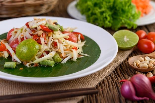 Salade de papaye (som tum thai) sur une plaque blanche sur une table en bois.