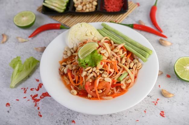 Salade de papaye thaï dans une assiette blanche avec du piment, du citron vert et de l'ail.