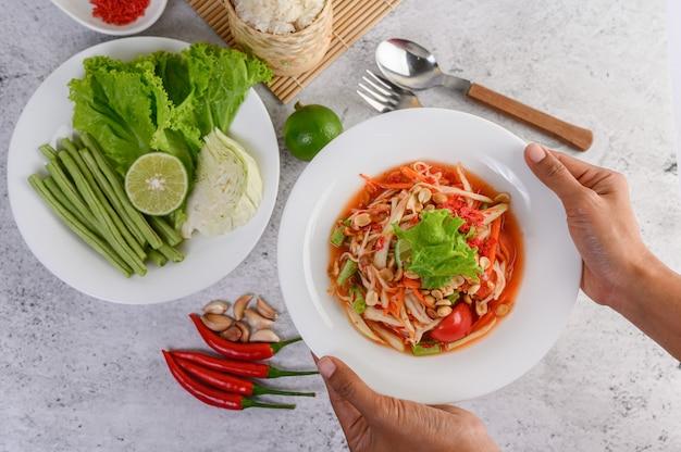 Salade de papaye thaïlandaise dans une assiette blanche avec du riz gluant et des crevettes séchées