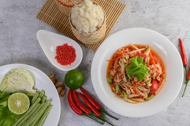 Salade de papaye thaïlandaise dans une assiette blanche avec du riz gluant dans un panier en osier de bambou et des crevettes séchées