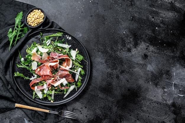 Salade de parme, jambon prosciutto, roquette et parmesan. fond noir, vue de dessus, espace pour le texte