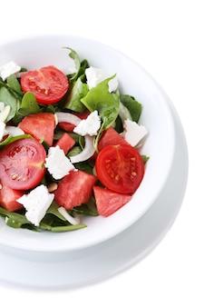 Salade de pastèque, feta, roquette et feuilles d'épinards sur plaque, isolé sur blanc