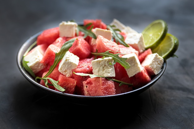 Salade de pastèque avec fromage feta, roquette et citron vert dans un bol