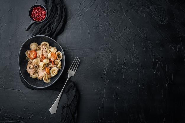 Salade de pâtes au thon et câpres bébé sur fond noir, vue du dessus