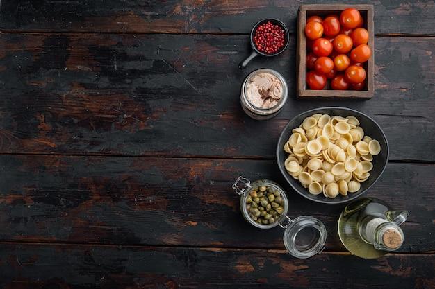 Salade de pâtes aux ingrédients du thon, sur une table en bois sombre, vue du dessus