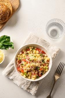 Salade de pâtes ditalini, pois, saucisse végétalienne sur table blanche moderne. fermer.