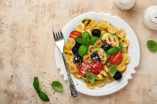 Salade de pâtes fiocchi aux légumes courgettes grillées, tomates cerises, olives, basilic et parmesan dans une assiette blanche sur fond d'ardoise claire, de pierre ou de béton. notion de déjeuner. vue de dessus.