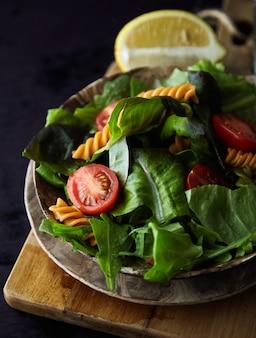 Salade de pâtes fusilli avec tomates colorées et feuilles de basilic sur bois foncé
