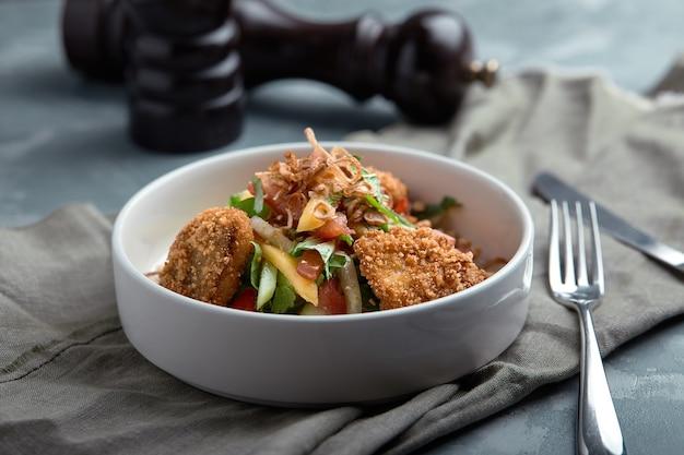 Salade de pépites de poulet frit et légumes sur fond gris
