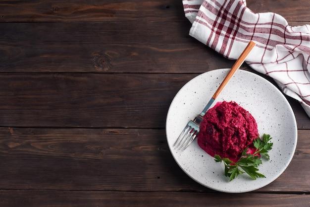 Salade de pignons de betterave râpés et persil avec sauce à la crème sur une assiette. espace copie vue de dessus