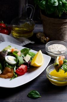 Salade sur plaque blanche, avec saumon et légumes sur table en bois foncé