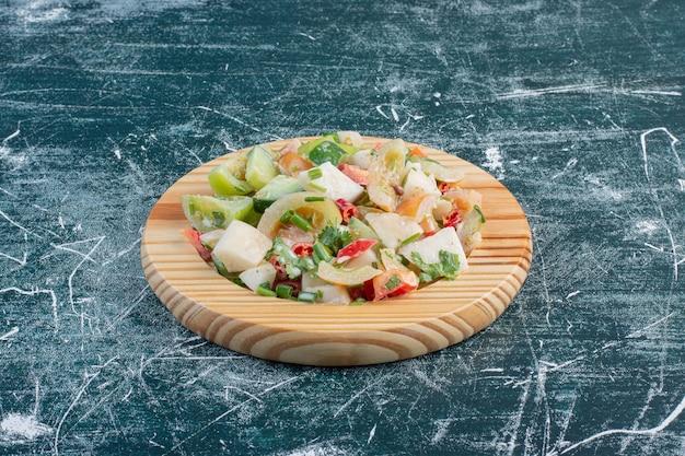 Salade sur un plateau en bois avec des ingrédients hachés et des herbes.