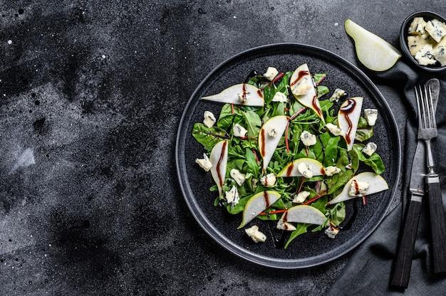 Salade de poire, fromage bleu, roquette et noix sur assiette. fond noir. vue de dessus. copiez l'espace.