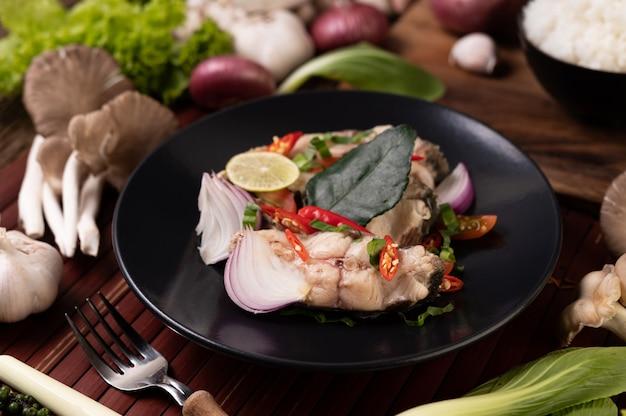 Salade de poisson au citron vert, chili, citronnelle, oignons, oignons rouges, persil et feuilles de lime kaffir dans l'assiette