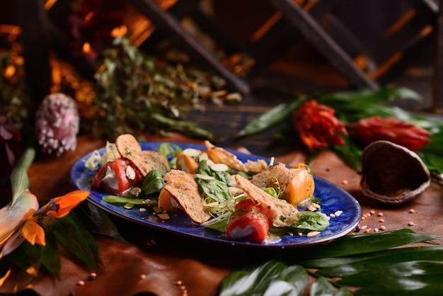 Salade de poisson, fromage à la crème et pain grillé. dans une assiette bleue. avec décor floral