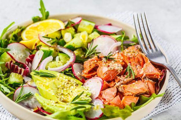Salade de poisson rouge cuite au four avec avocat, concombre, radis et roquette dans une assiette blanche.