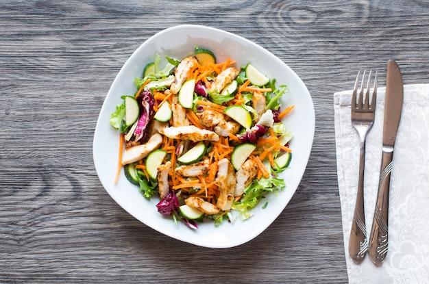 Salade de poitrine de poulet aux courgettes et tomates cerises sur un fond en bois