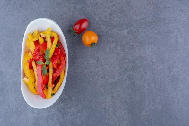 Salade de poivrons colorés aux tomates cerises sur une surface bleue