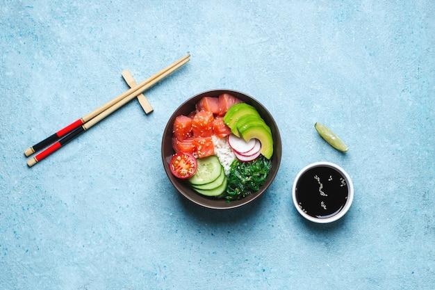 Salade de poke de saumon hawaïen, baguettes et sauce soja sur fond bleu.