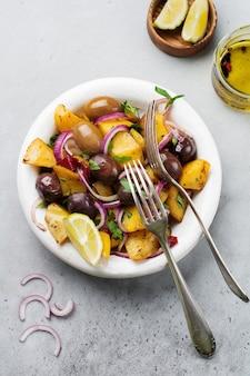 Salade de pommes de terre tiède aux olives, poivrons, persil et oignon rouge sur une vieille plaque en céramique blanche sur une surface de béton gris. mise au point sélective. vue de dessus. copiez l'espace.
