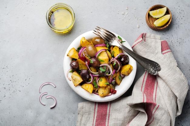 Salade de pommes de terre tiède aux olives, poivrons, persil et oignon rouge sur une vieille plaque en céramique blanche sur une surface de béton gris