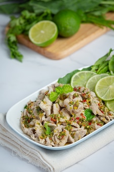 Salade de porc épicée servie avec des tiges de chou frisé frais et croustillant cuisine thaïlandaise.