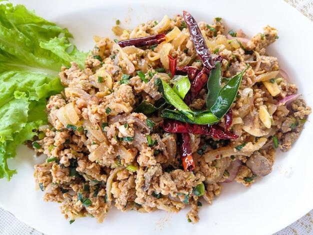 Salade de porc hachée épicée sur une assiette blanche avec du piment séché aux légumes frais et de la laitue