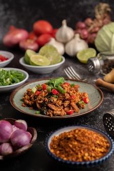 Salade de porc hachée épicée avec flocons de piment, citron vert, oignons verts hachés, piment et riz rôti, échalotes tranchées sur un sol en ciment.