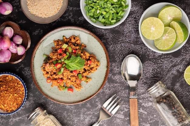 Salade de porc hachée épicée avec flocons de piment, citron vert, oignons verts hachés