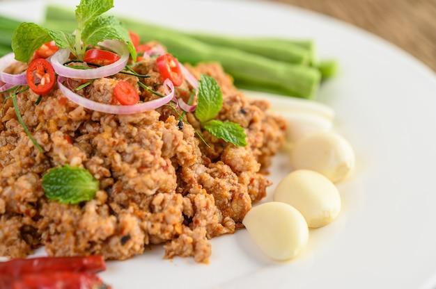 Salade de porc hachée épicée sur une plaque blanche avec des lentilles, des feuilles de lime kaffir et des oignons de printemps.