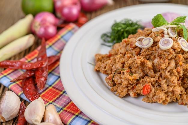 Salade de porc hachée épicée sur une plaque blanche avec oignon rouge, citronnelle, ail, haricots verts, feuilles de lime kaffir et oignon de printemps