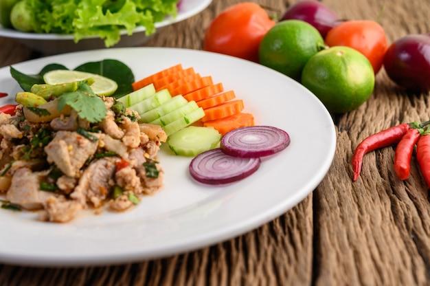 Salade de porc hachée épicée sur une plaque blanche sur une table en bois.