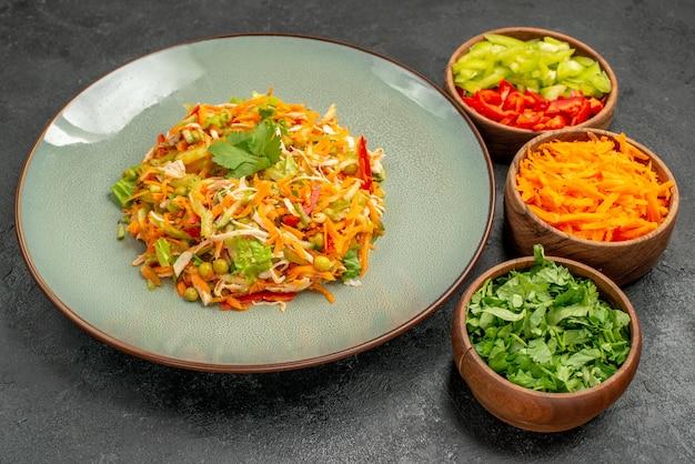 Salade de poulet aux légumes vue de face avec des verts sur une table grise régime alimentaire santé salade
