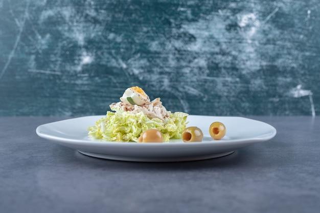 Salade de poulet bouilli et d'oeufs sur une assiette blanche.