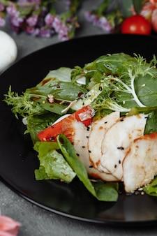 Salade de poulet fumé sur une plaque noire.