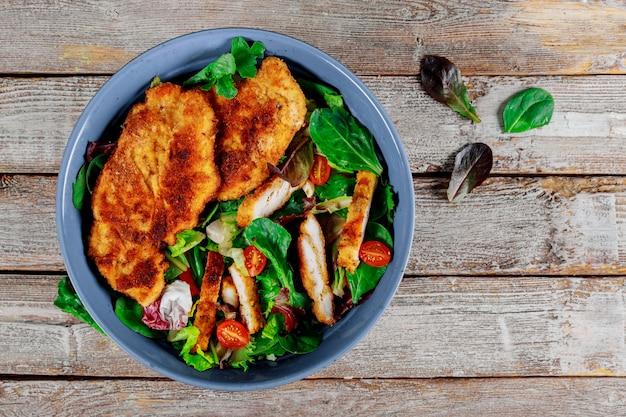 Salade de poulet grillé avec des légumes frais sur fond en bois ancien.