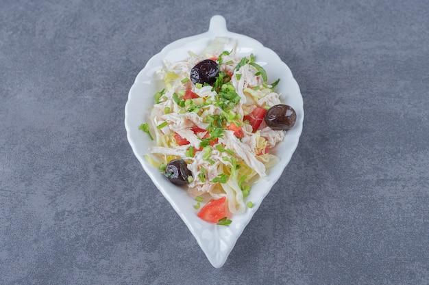 Salade de poulet maison sur plaque en forme de feuille.