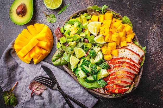 Salade de poulet, mangue et avocat grillé dans un plat noir sur fond sombre, vue de dessus.