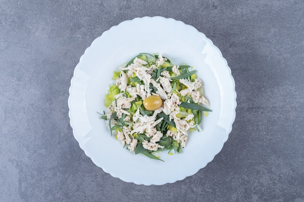Salade de poulet en tranches sur plaque blanche.